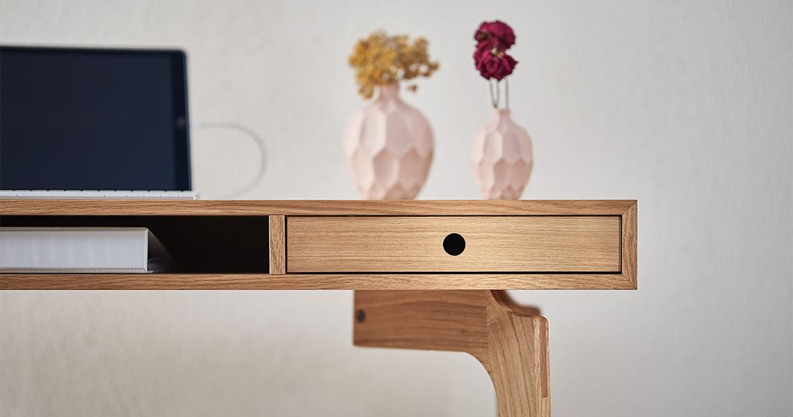 Nahaufnahme eines Schreibtisches aus Holz mit einem Tablet und einer Vase