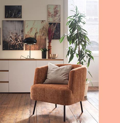 Hellbrauner Sessel mit Stoffbezug auf Holzboden neben grüner Zimmerpflanze