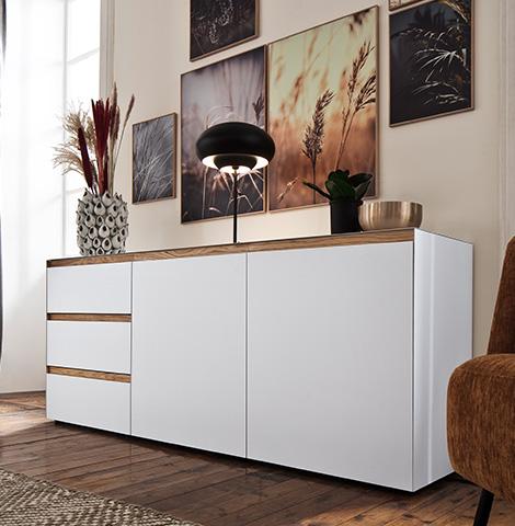 Weißes Sideboard mit Griffleisten aus Holz dekoriert mit einer Lampe und einer Vase