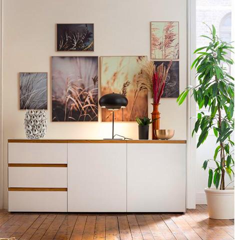 Weißes Sideboard mit braunen Griffleisten in einem erdfarben-eingerichtetem Zimmer