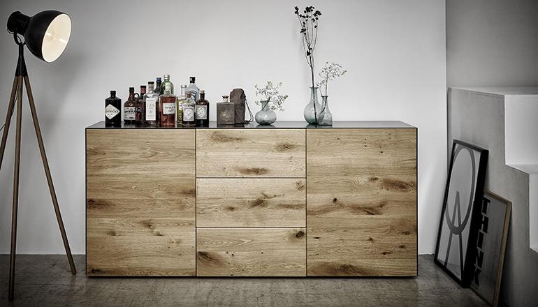 Modernes Sideboard mit Fronten aus Massivholz dekoriert mit Flaschen und Vasen
