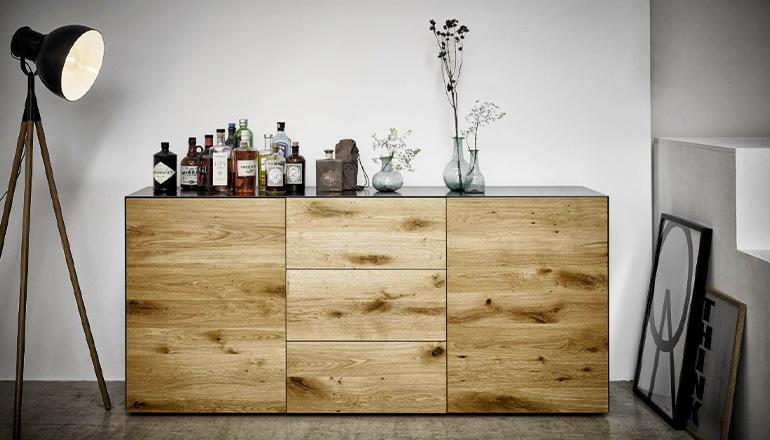 Sideboard aus Massivholz und schwarzem Metall mit einer Reihe von alkoholischen Getränken