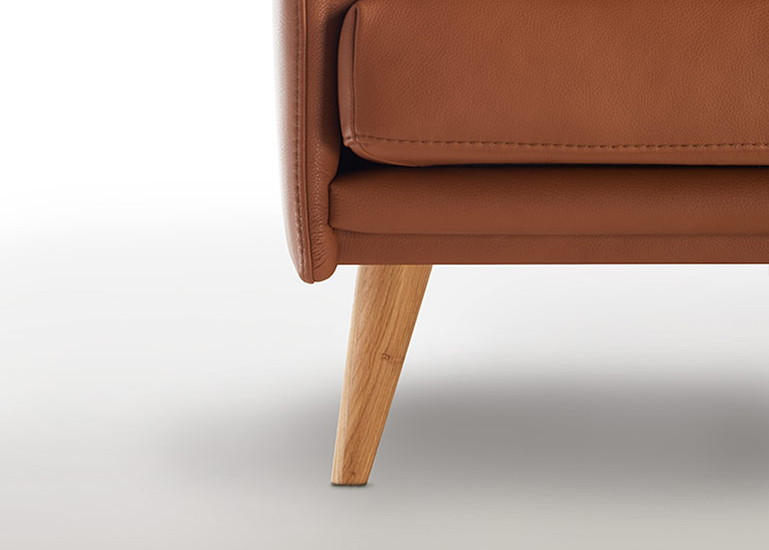 Ein abstehender Holzfuß kombiniert mit einer braunen Couch