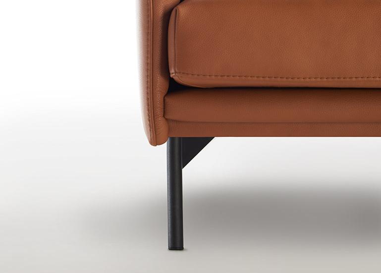 Ein gerader, schwarzer Metallfuß kombiniert mit einer braunen Couch