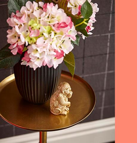 Goldener Affe vor einer schwarzen Vase mit rosa Blumen auf einem Beistelltisch