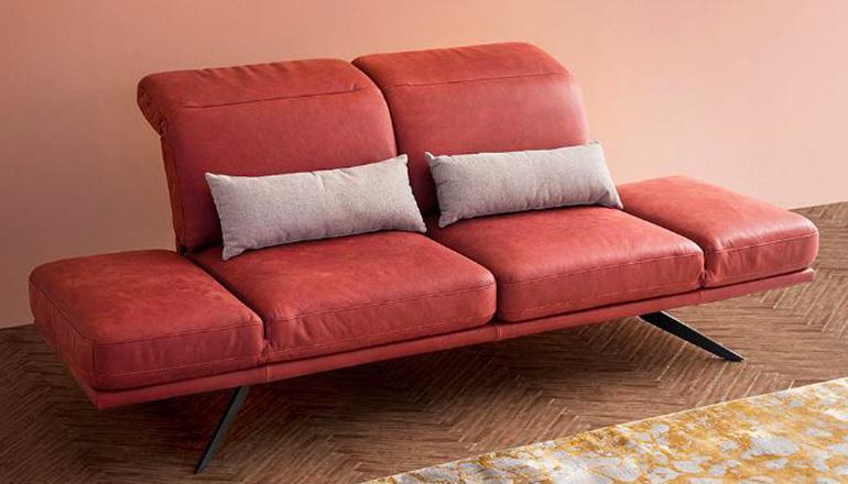 Rotes Sofa mit zwei grauen Deko-Kissen auf einem Fischgrätparkett