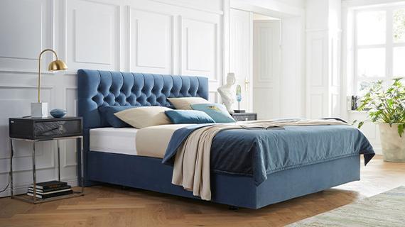 Blaues Boxspringbett mit sattem Blau für den Stoffbezug im eleganten Schlafzimmer