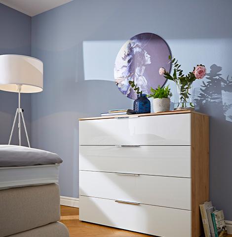 Weiße Kommode mit hölzernem Korpus vor einer blauen Wand