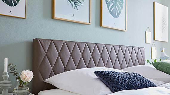 Blaues Kissen in einem Bett mit einem brauen Kopfteil aus Leder und weißer Bettwäsche
