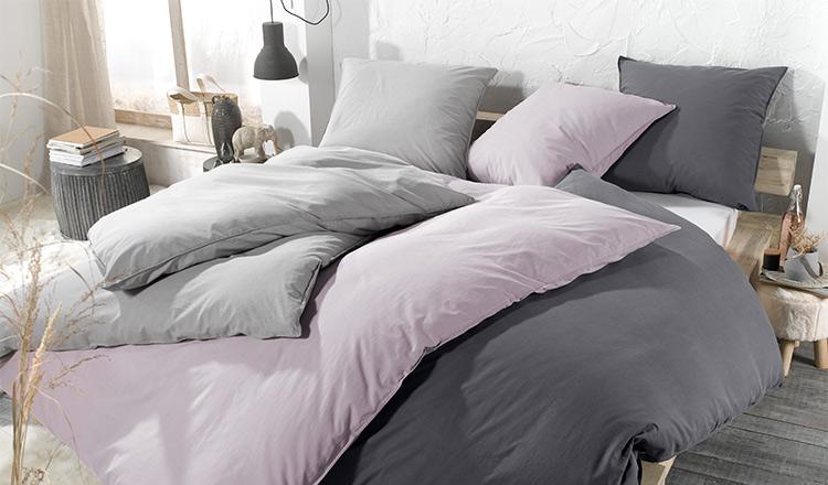 Bettwäsche in drei verschiedenen Farben auf einem Bett mit Holzgestell