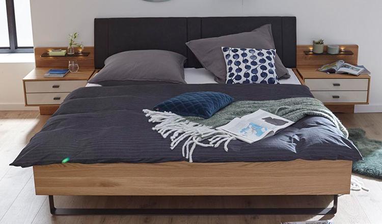 Hölzernes Bettgestell mit Kufengestell, Polster am Kopfende und grauer Bettwäsche