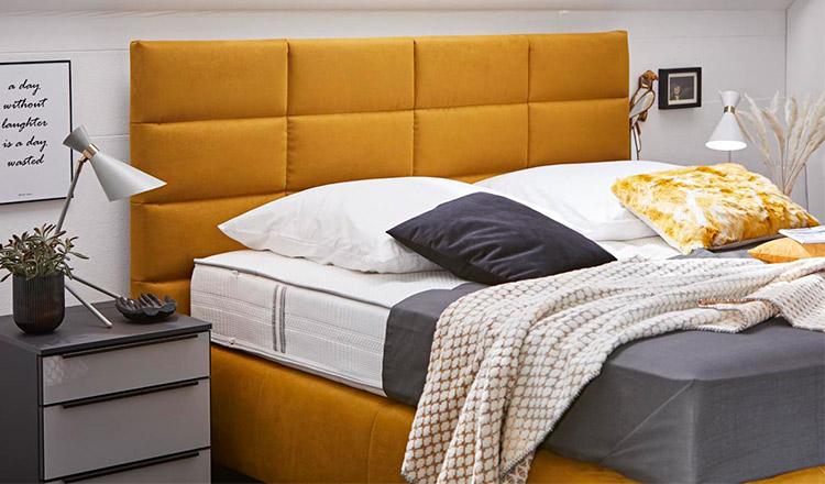 Gelbes Boxspringbett mit verschiedenen Kissen und einer gemusterten Wohndecke