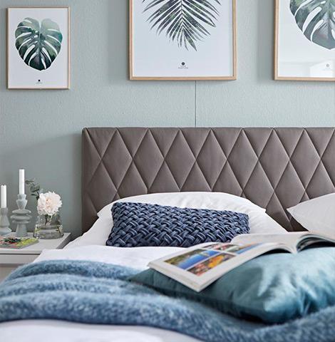 Graues Polster am Kopfteil eines Bettgestells mit blauen Deko-Kissen und weißer Bettwäsche