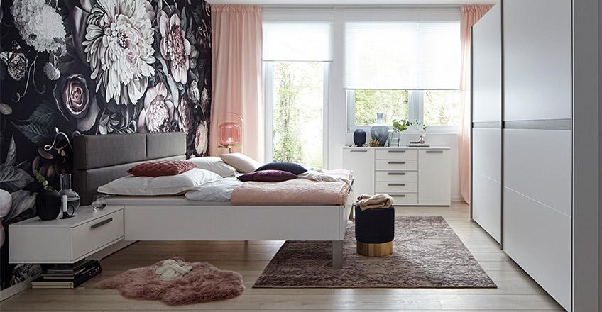 Weißes Bett mit gepolstertem Kopfteil vor bunter Blumentapete