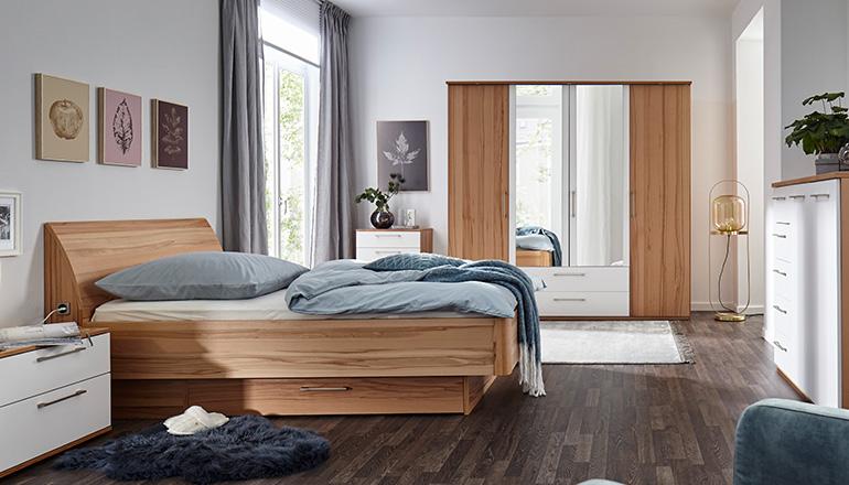 Schlafzimmer mit Holzmöbeln wie einem Bett, Drehtürenschrank und Kommode