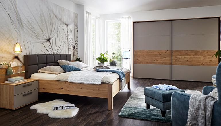 Schlafzimmer in Holzoptik mit einem Bettgestell und Kleiderschrank sowie Nachtkästchen