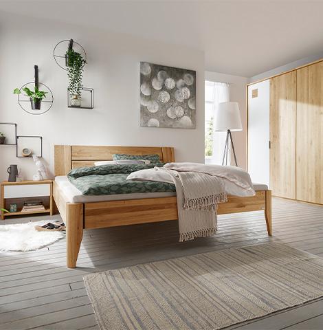 Bettgestell aus massiver Eiche in einem hellen Schlafzimmer mit Kleiderschrank und Stehleuchte