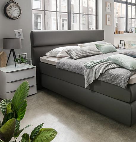 Klassischer Nachttisch neben einem grauen Boxspringbett mit blauer Bettwäsche