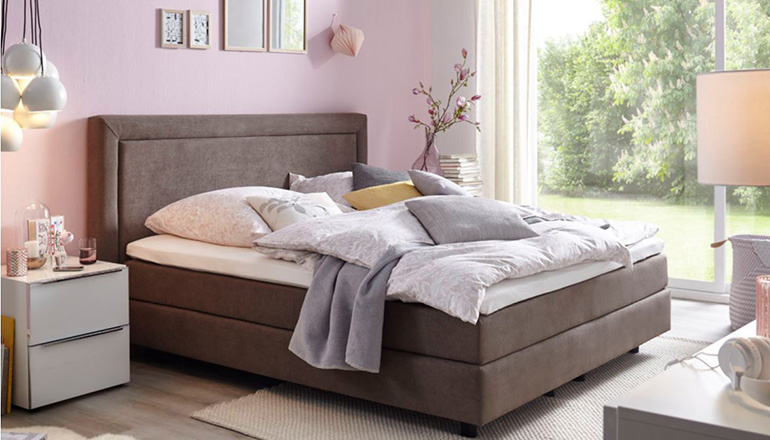 Braunes Boxspringbett mit heller Bettwäsche und vielen Kissen vor eine rosa Wand