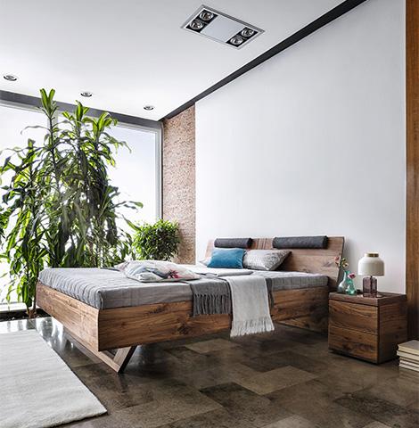 Schönes Bett aus elegantem Nussbaum Massivholz neben großer Zimmerpflanze
