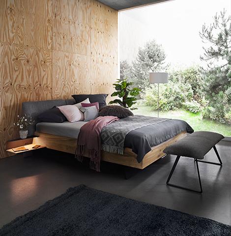 Bett aus Massivholz mit einem gepolstertem Kopfteil mit Wolle-Bezug