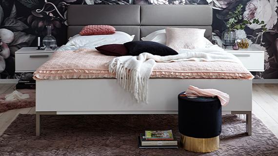 Schwarz-goldener Hocker vor einem weißen Bettgestell mit rosafarbener Bettwäsche
