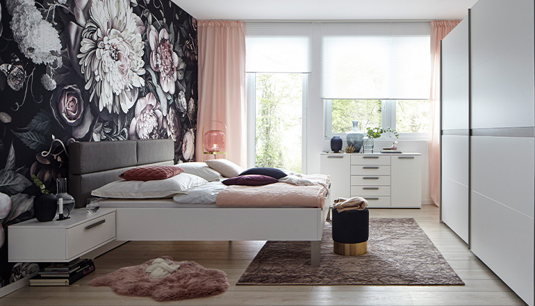 Weißes Bett vor einer blumigen Tapete und einer weißen Kommode sowie Kleiderschrank in Weiß