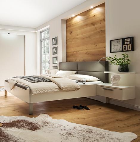 Weißes Bettgestell mit grauem gepolsterten Kopfteil im modernen Schlafzimmer