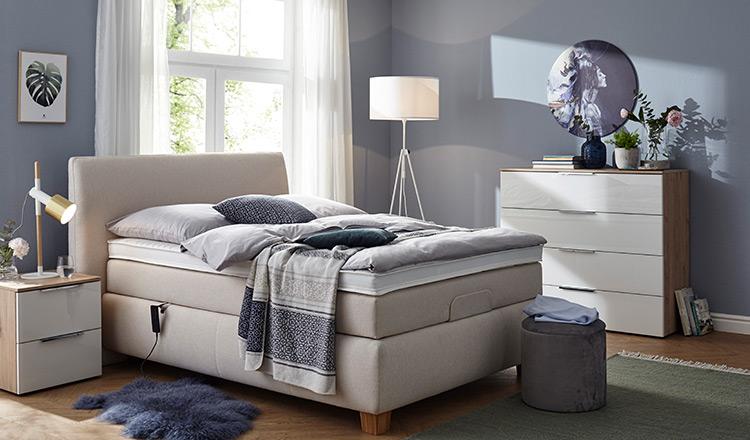 Beiges Boxspringbett neben einem Nachttisch und Sideboard mit weißer Lackfront