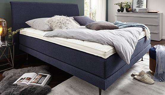 Dunkelblaues Boxspringbett mit grauer Bettdecke und grauen Deko-Kissen