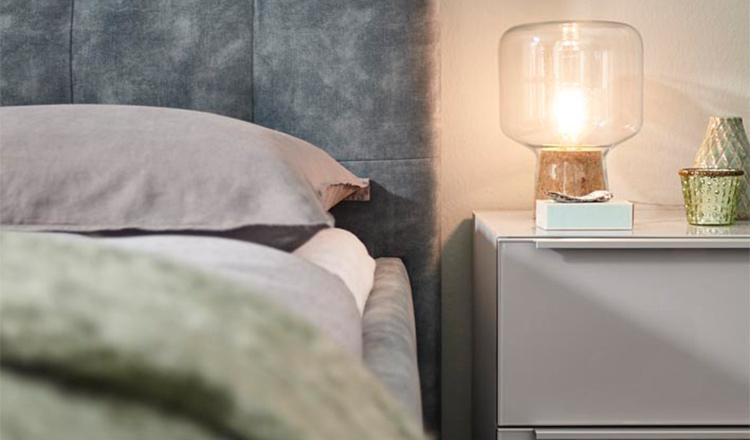 Grauer Nachttisch mit einer Lampe neben einem grauen Bettgestell mit Bettwäsche