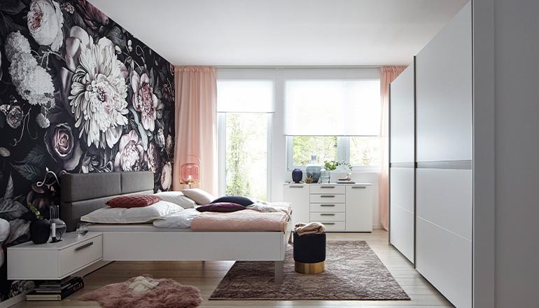 Weißer Kleiderschrank mit Schwebetüren vor Bett und einer bunten Blumentapete