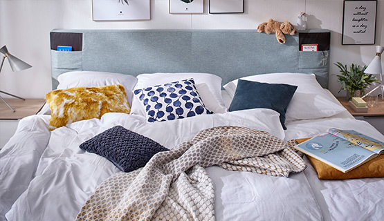 Blaues Boxspringbett mit weißer Bettdecke und vielen bunten Kissen