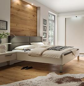 Modernes Bett mit grauem Polster am Kopfende vor einer Holzwand
