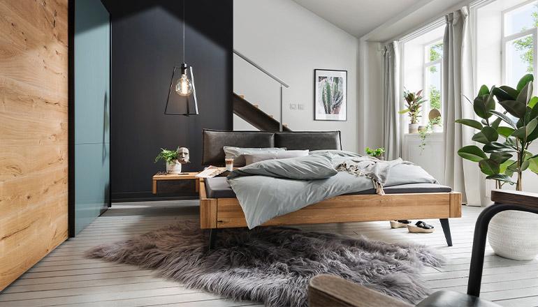 Schlafzimmer mit Holzbett und Kleiderschrank aus Furnier