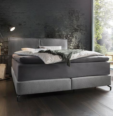 Elegantes Boxspringbett mit dunkler Bettwäsche und einem Spannbettlaken für Toppermatratzen