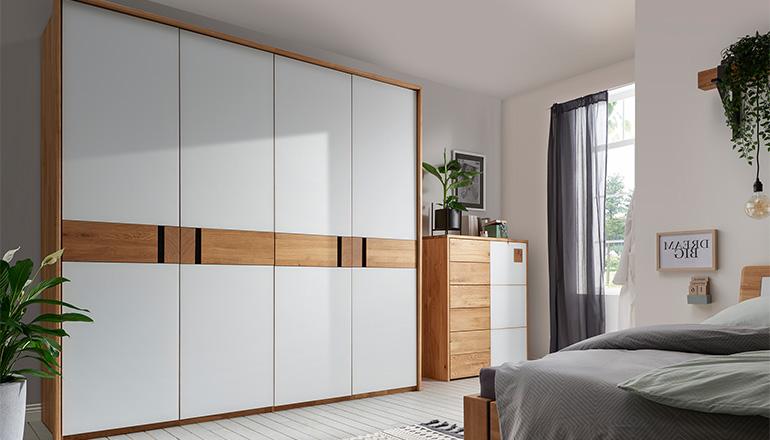 Drehtürenschrank mit Holz-Elementen und weißem Lack im natürlich eingerichteten Schlafzimmer