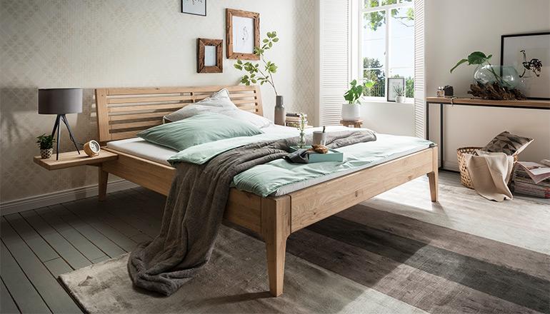 Massivholz-Bettgestell mit einem Kopfteil aus Sprossen und türkise Bettwäsche