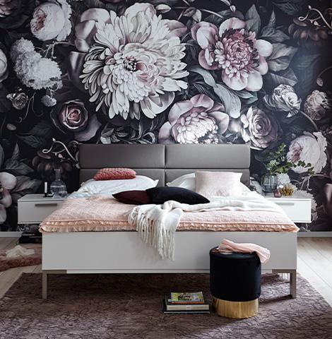 Weißes Bettgestell vor bunter Tapete mit vielen Blumen