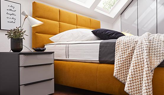 Gelbes Boxspringbett neben einem grauen Nachttisch mit einer modernen Lampe