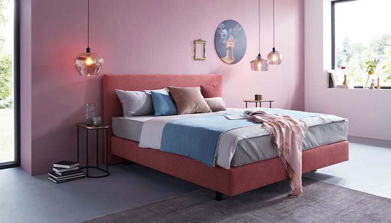 Boxspringbett in einem dunklen Rosé vor einer rosafarbenen Wand