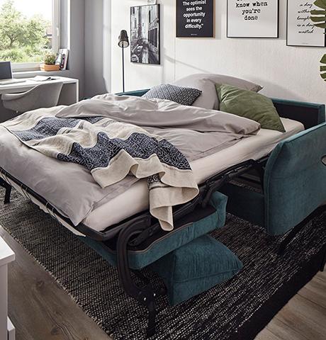 Blaues Funktionssofa umgebaut in ein Bett mit grauer Bettwäsche