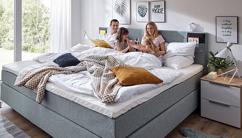 Vierköpfige Familie sitzt in einem großen, grauen Boxspringbett mit bunten Deko-Kissen