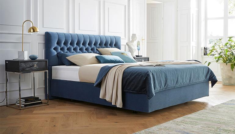 Blaues Boxspringbett vor weißer Wand und weißer Deko