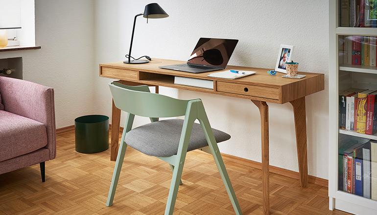 Heller Schreibtisch aus furnierter Eiche vor mintgrünem Stuhl