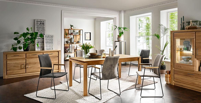 Esszimmer mit Möbeln aus massivem Holz und Armlhenstühlen aus Leder