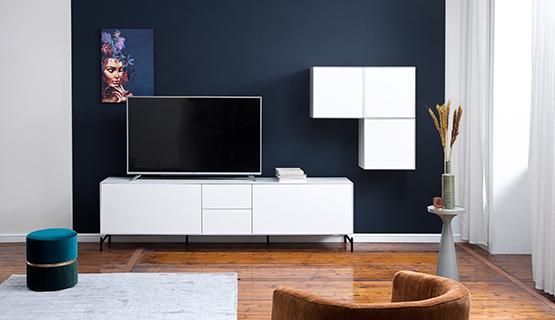 Weißes Skandi-Lowboard mit dreigliedrigem Wandregal, Fernseher vor blauem Hocker mit braunem Sessel