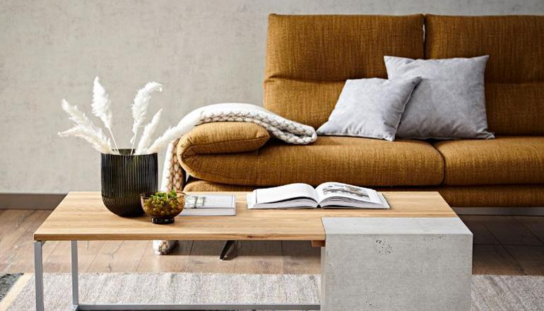 Gold-braunfarbenes Sofa vor Couchtisch mit Holz- und Beton-Elementen
