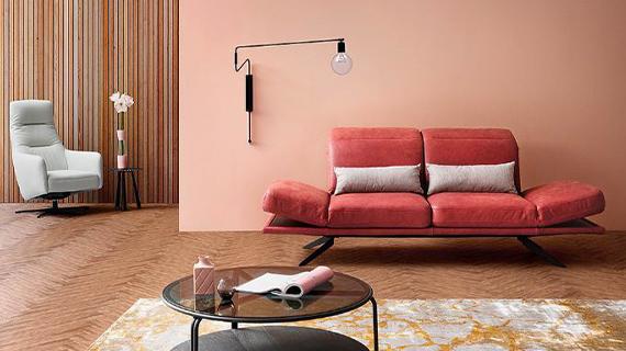 Rote Zweisitzer Couch und ein weißer Relaxsessel vor rosafarbener Wand