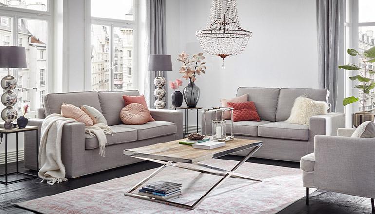 Sofa Garnitur in Hellgrau mit rosa Kissen unter einem Kronleuchter